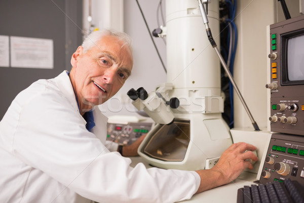 Stock photo: Biochemist using large microscope and computer