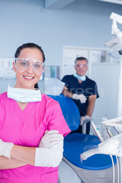 Smiling assistant and dentist behind her with protective glasses Stock photo © wavebreak_media