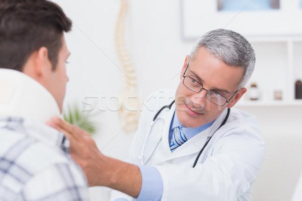 Doctor examining patient wearing neck brace Stock photo © wavebreak_media