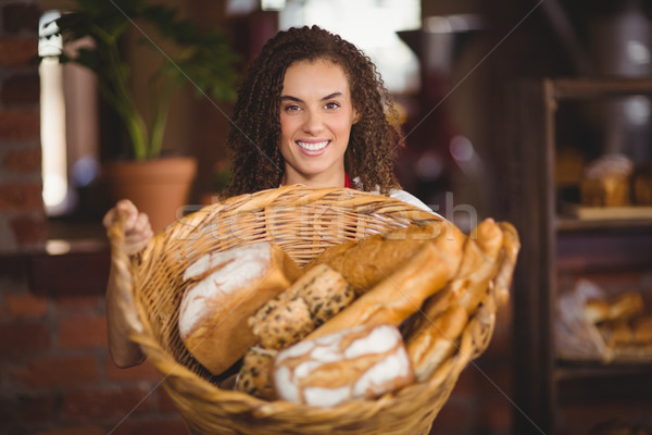 Smiling waitress showing a basket of bread Stock photo © wavebreak_media