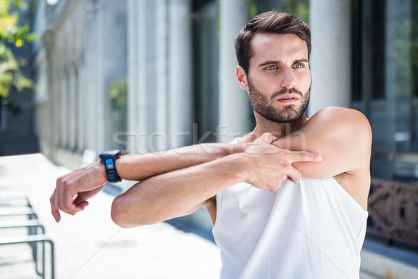 Focused handsome athlete stretching his arm Stock photo © wavebreak_media