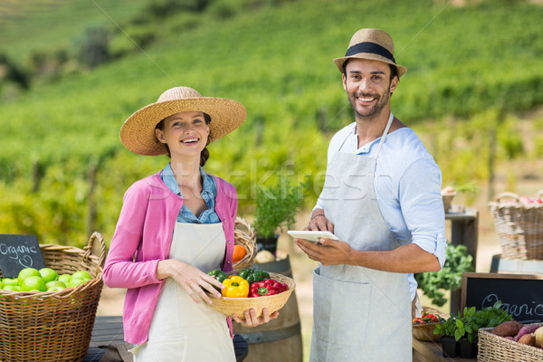 Happy couple holding bell peppers in basket with digital tablet Stock photo © wavebreak_media