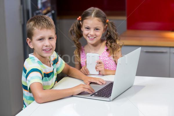 Glimlachend broers en zussen met behulp van laptop keuken portret home Stockfoto © wavebreak_media