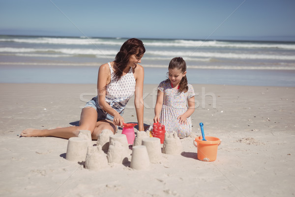 Happy girl with mother making sand castle at beach Stock photo © wavebreak_media