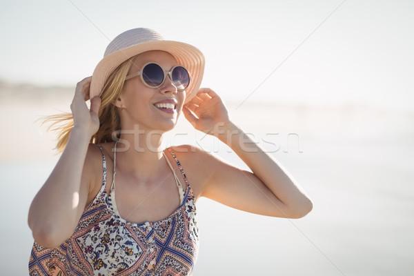 Fiatal nő visel napszemüveg kalap tengerpart napos idő Stock fotó © wavebreak_media
