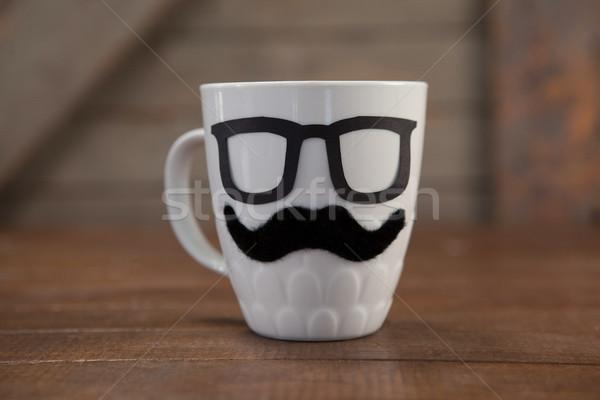 Coffee mug with mustache and eyeglasses on table Stock photo © wavebreak_media