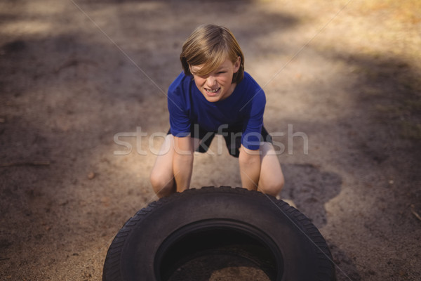 Determined girl exercising with huge tyre during obstacle course Stock photo © wavebreak_media