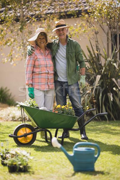 Portrait of smiling senior couple standing by wheel borrow in yard Stock photo © wavebreak_media