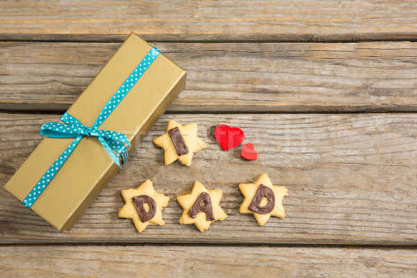 Overhead view of gift box by coockies with text obn table Stock photo © wavebreak_media