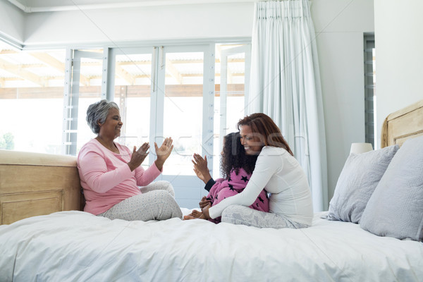 Family playing clapping games on bed in bedroom Stock photo © wavebreak_media