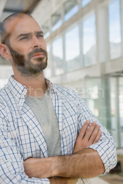 Thoughtful male designer with arms crossed seen through glass Stock photo © wavebreak_media