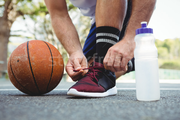 Low section of basketball player tying shoelace Stock photo © wavebreak_media