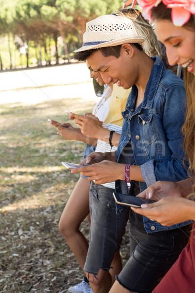 Smiling fiends using mobile phone while standing by camper van Stock photo © wavebreak_media