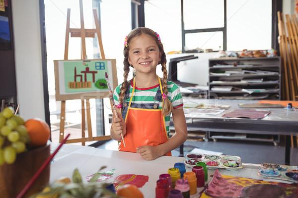 Porträt Mädchen glücklich halten Pinsel stehen Schreibtisch Stock foto © wavebreak_media