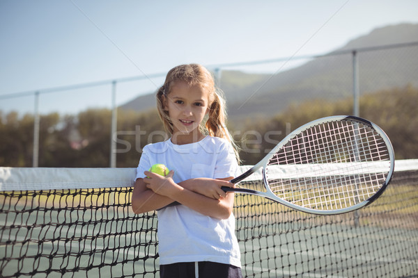 Confident girl holding tennis racket and ball at court Stock photo © wavebreak_media