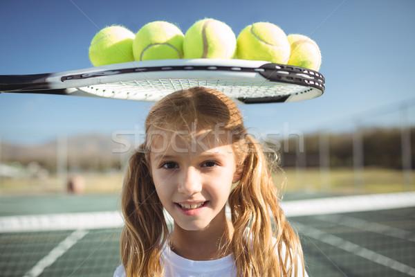 Smiling girl standing below tennis racket and balls Stock photo © wavebreak_media