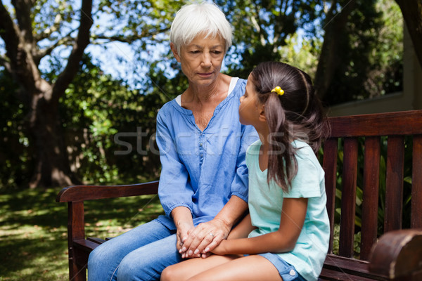 Grandmother and granddaughter holding hands while sitting on bench Stock photo © wavebreak_media