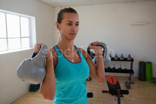 Confident female athlete lifting kettlebells in gym Stock photo © wavebreak_media