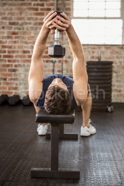 Man lifting dumbbell while lying on bench Stock photo © wavebreak_media