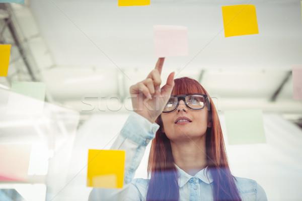 Attrattivo donna punta note adesive ufficio Foto d'archivio © wavebreak_media
