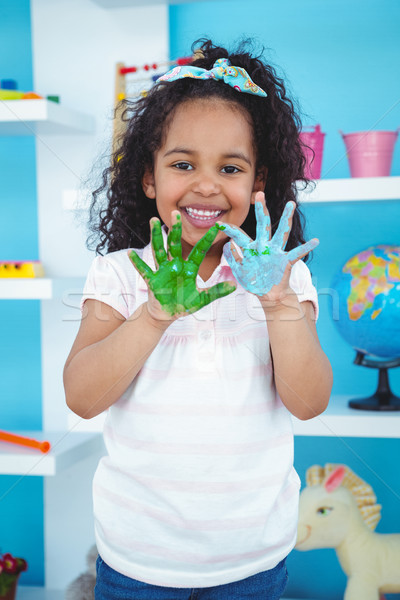 Cute girl showing her paint covered hands Stock photo © wavebreak_media