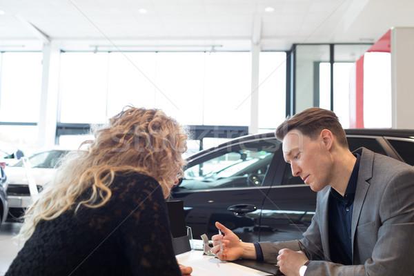 Salesman discussing over document with customer in showroom Stock photo © wavebreak_media