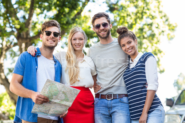 Hip friends holding map and smiling at the camera Stock photo © wavebreak_media