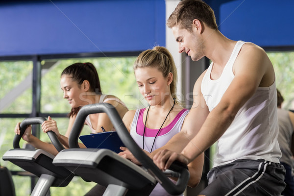Trainer woman talking with a man doing exercise bike Stock photo © wavebreak_media