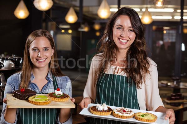 Smiling baristas holding desserts Stock photo © wavebreak_media