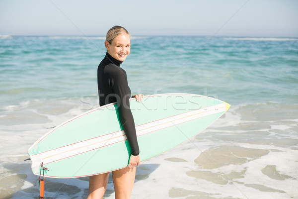 Woman in wetsuit holding a surfboard on the beach Stock photo © wavebreak_media