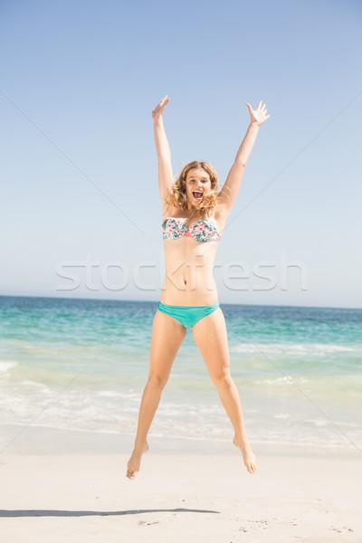 Stock photo: Carefree woman in bikini jumping on the beach