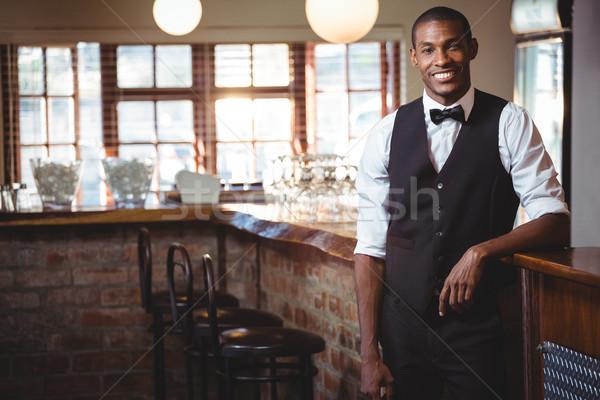 Portrait of bartender standing at bar counter Stock photo © wavebreak_media