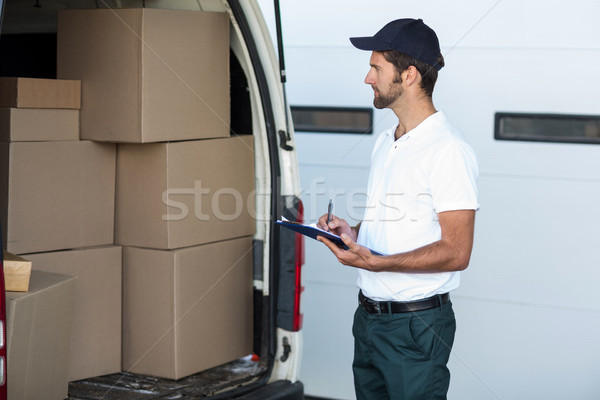 Stock photo: Delivery man is looking his goods and holding a clipboard