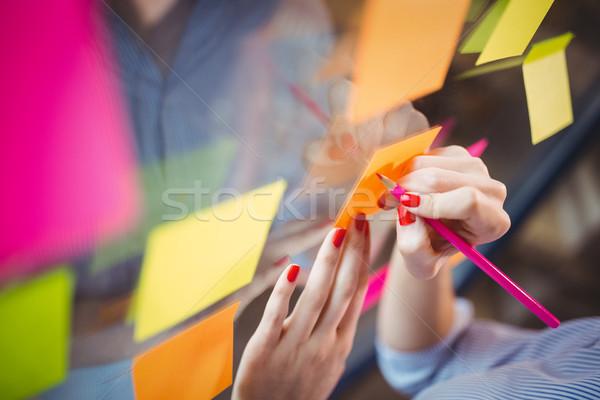 Kobieta interesu piśmie karteczki szkła obraz Zdjęcia stock © wavebreak_media