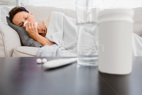 Mature woman sneezing  with medicine on foreground Stock photo © wavebreak_media