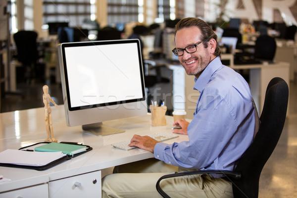 Businessman sitting at computer desk  Stock photo © wavebreak_media