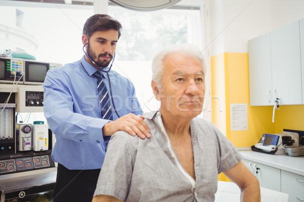 Male doctor examining a patient Stock photo © wavebreak_media