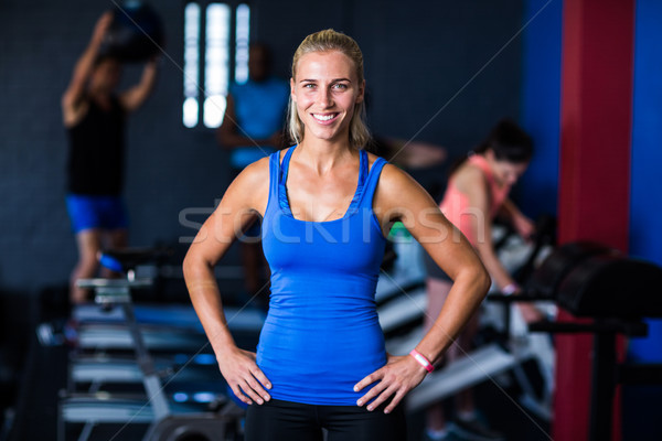Portrait of happy fit woman with hands on hip in gym Stock photo © wavebreak_media