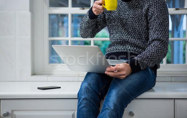 Man met behulp van laptop koffie keuken home Stockfoto © wavebreak_media