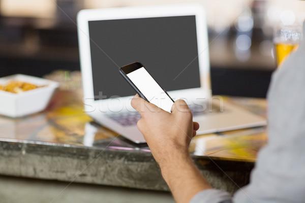 Férfi mobiltelefon laptop asztal bár pult Stock fotó © wavebreak_media