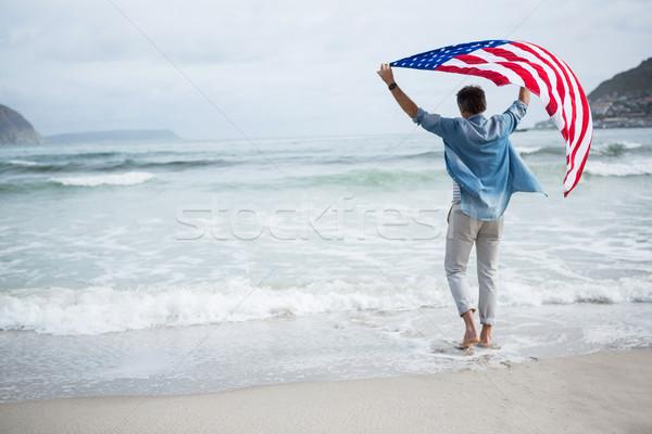 Hátsó nézet férfi tart amerikai zászló tengerpart égbolt Stock fotó © wavebreak_media