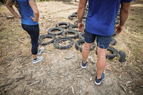 Man and woman standing near tyre during obstacle course Stock photo © wavebreak_media