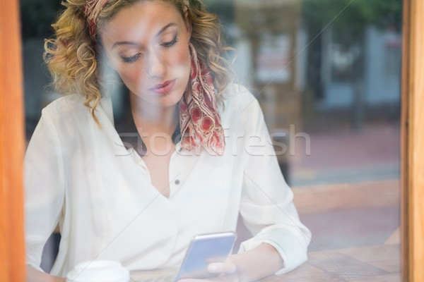 Woman using smart phone in cafe seen through window Stock photo © wavebreak_media