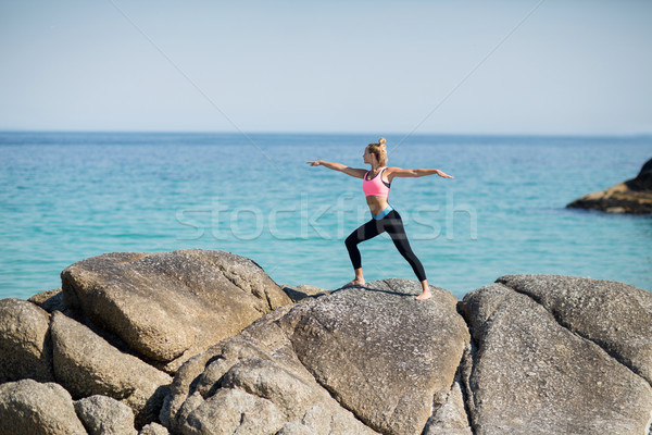 Woman practicing warrior pose on rocky shore Stock photo © wavebreak_media