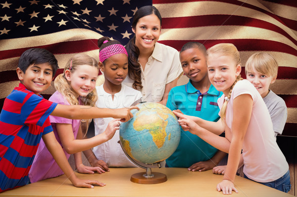 Stock photo: Composite image of cute pupils and teacher looking at globe in l