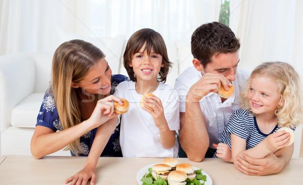 Loving family eating burgers in the living room Stock photo © wavebreak_media