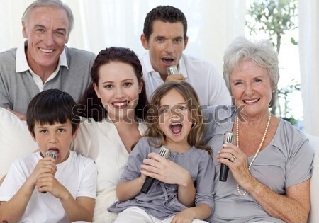Family singing karaoke at home Stock photo © wavebreak_media