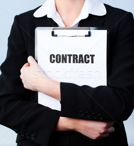 Woman holding a contract on a clipboard Stock photo © wavebreak_media
