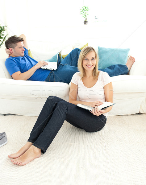 Cute couple reading book in the living-room Stock photo © wavebreak_media