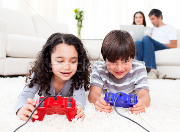 Cute siblings playing video games laying down on the floor Stock photo © wavebreak_media